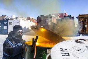 Jean-Yves, technicien polyvalent, permanent de l'IPEV, effectue sa premiere campagne d'ete a Concordia. Il decoupe au chalumeau d'anciens futs pour les recycler en poubelles.